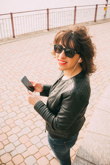 Portrait Of Smiling Mid Adult Woman Using Mobile Phone On Footpath
