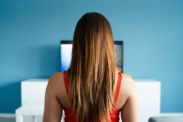 Rear view of woman watching tv while sitting on sofa at home