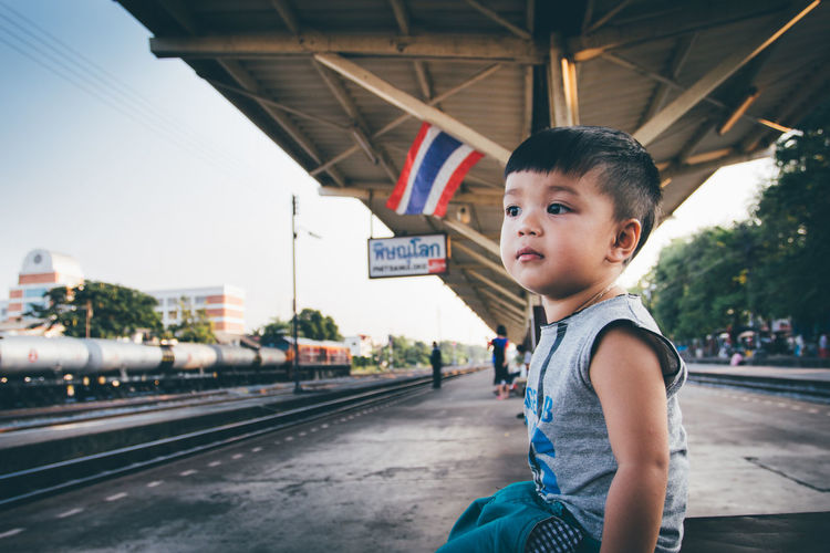 Side view of boy sitting at railroad station platform