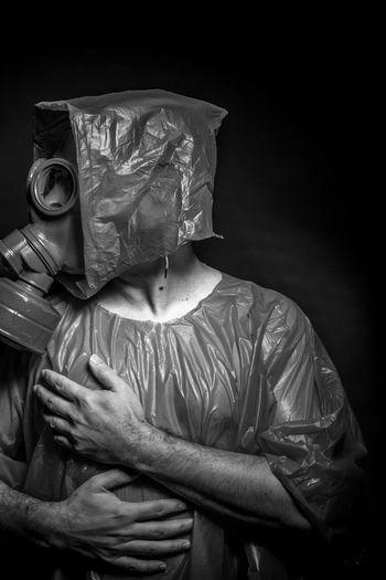 Man In Raincoat Wearing Gas Mask Against Black Background