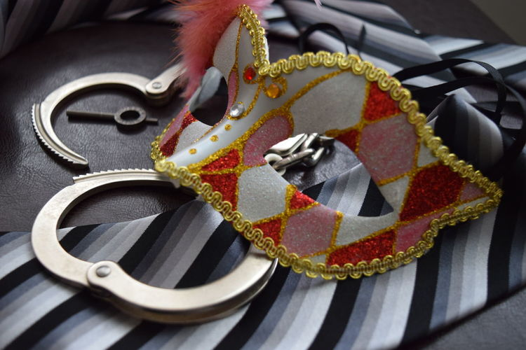 Close-up of masquerade mask and handcuffs on leather