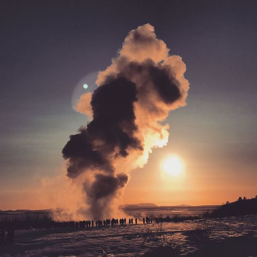 Steam Emitting From Geyser Against Sky During Sunset