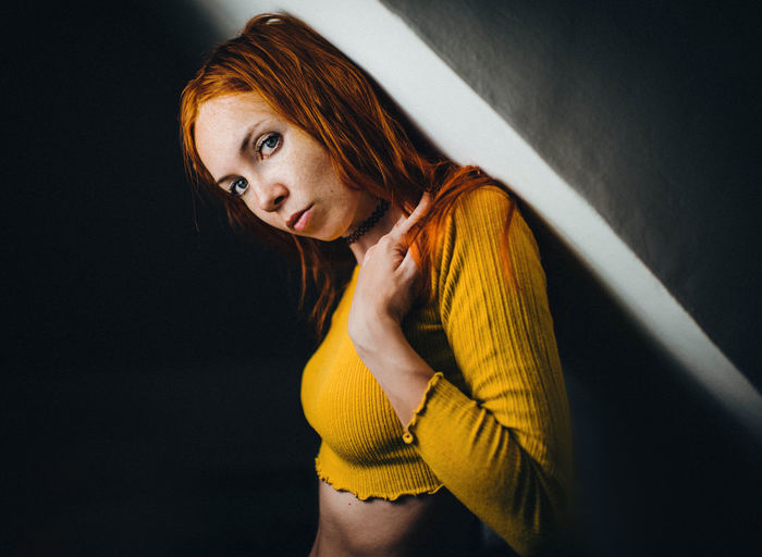 Portrait of woman leaning on wall