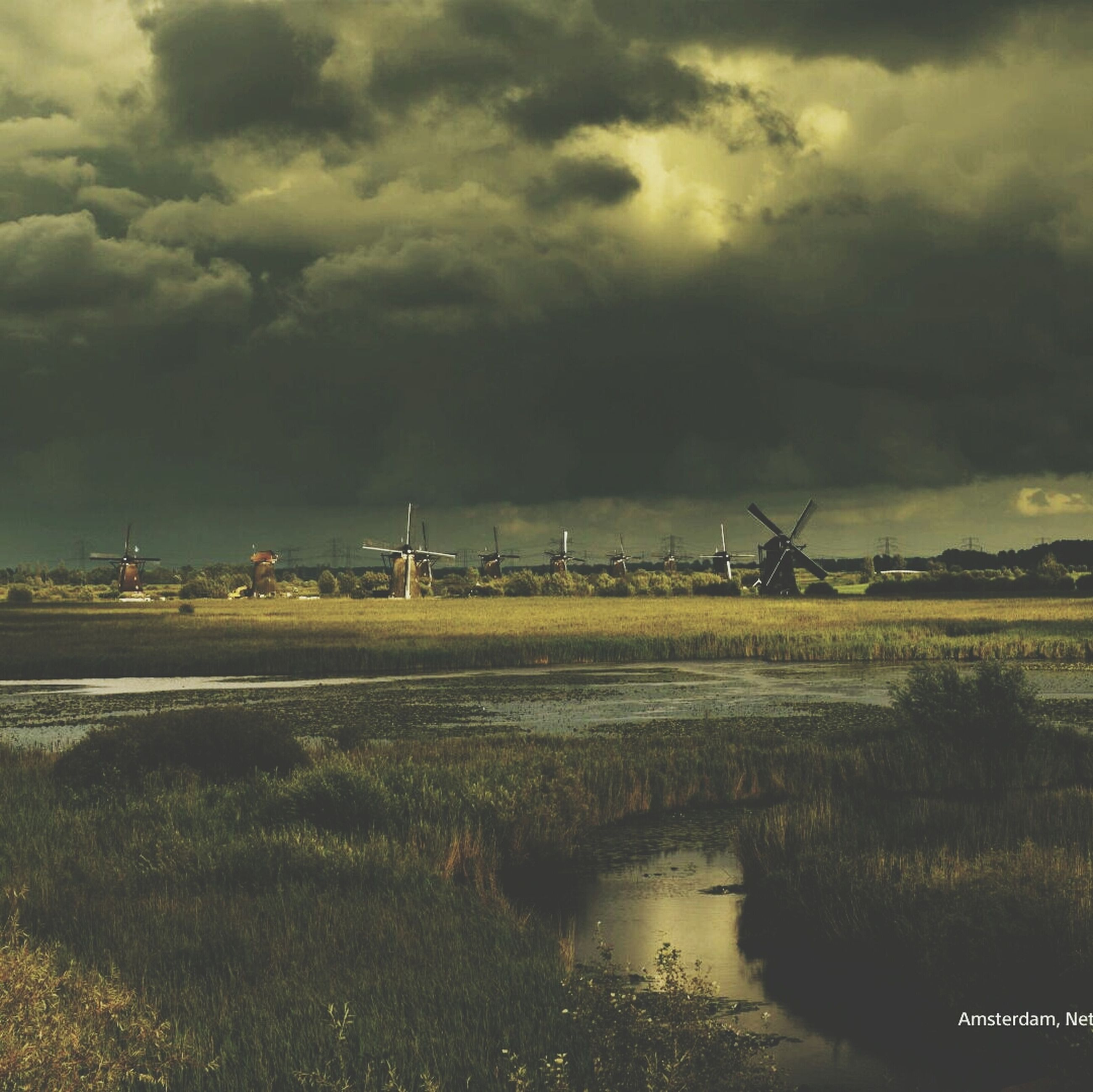 sky, cloud - sky, cloudy, weather, water, tranquil scene, tranquility, overcast, nature, scenics, landscape, beauty in nature, cloud, storm cloud, grass, field, river, outdoors, dusk, transportation