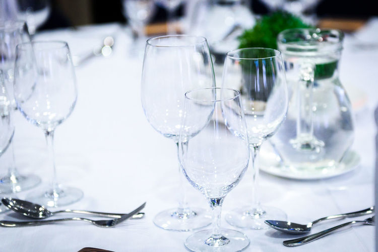 Transparent glasses on a banquet table with spoons and forks. Preparing the table for fancy, luxury catering event with cutlery and white tablecloth. Scene from wedding or business event. Wine Glass Alcohol Buffet Celebration Champagne Flute Cutlery Drinking Glass Elégance Focus On Foreground Food Food And Drink Glass No People Place Setting Plate Preparing Food Restaurant Still Life Table Wedding White Wine Wine Wineglass