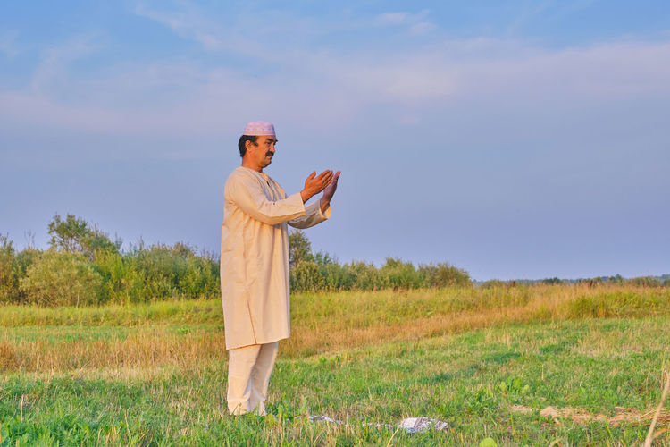 A muslim senior man wearing a skullcap and traditional white clothes prays in an agricultural field