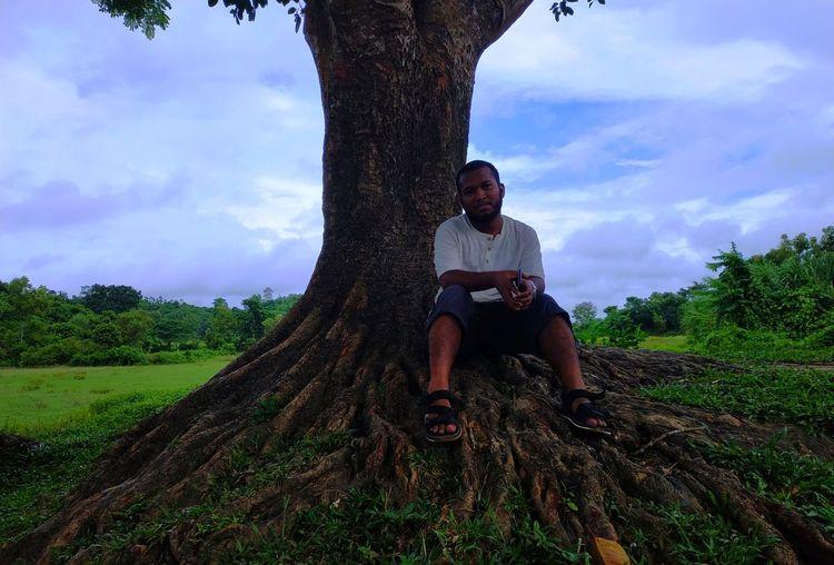 Full Length Of Man Sitting By Tree Against Sky