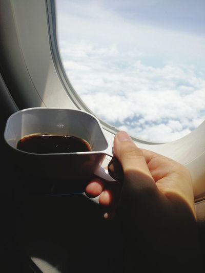Hand holding coffee cup against window