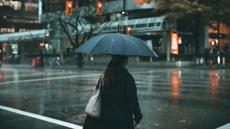 Woman walking on wet road during rainy season