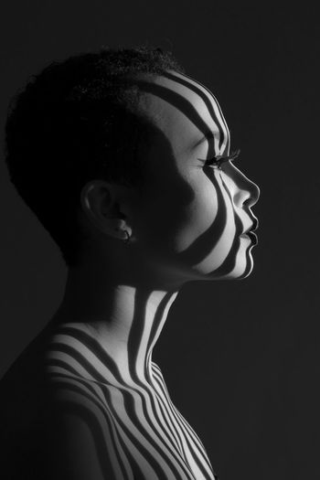 Side view of topless thoughtful young woman against black background