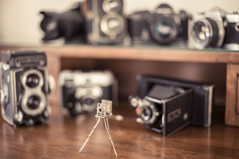 Miniature and old vintage cameras on wooden table