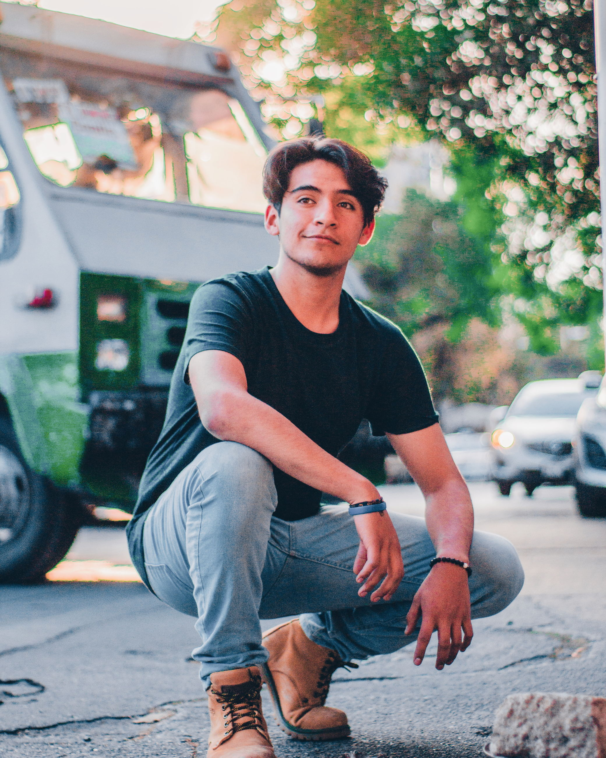 one person, casual clothing, real people, looking at camera, full length, transportation, mode of transportation, young adult, young men, portrait, day, lifestyles, land vehicle, sitting, front view, men, leisure activity, city, outdoors