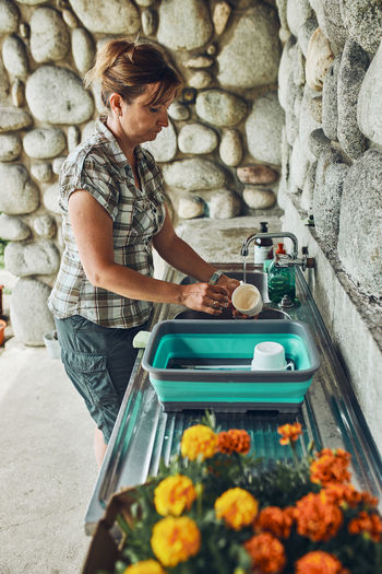 Woman washing up the dishes pots and plates in the outdoor kitchen during vacations on camping