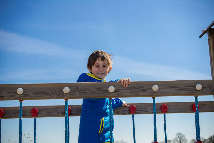 Portrait of smiling boy standing amidst railings against blue sky
