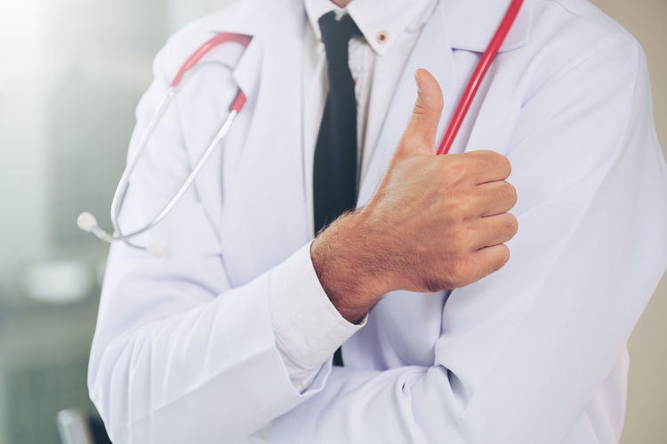 Midsection of doctor showing thumbs up