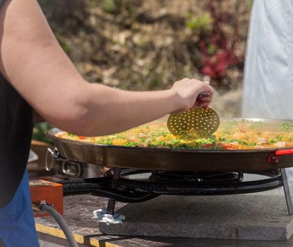 Midsection Of Woman Preparing Food On Stove Burner Outdoors