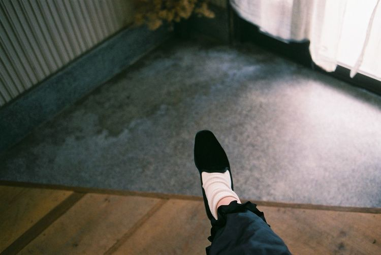 Low section of person wearing shoes on floor