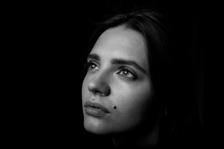 Close-up of young woman looking away against black background