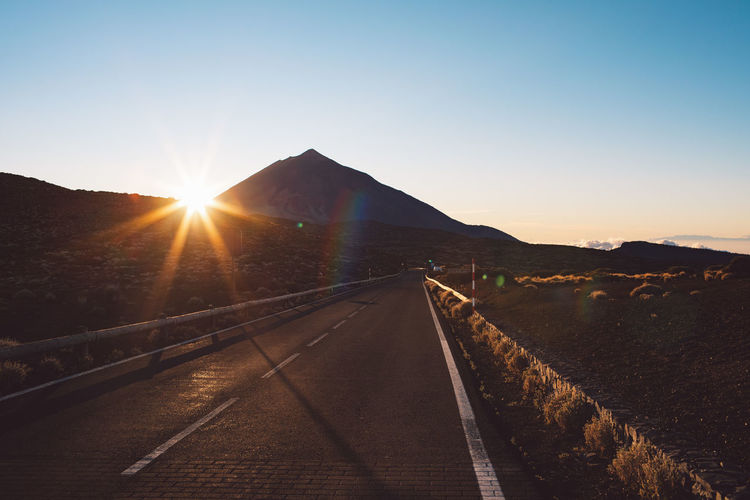 Road leading towards mountains against clear sky during sunset