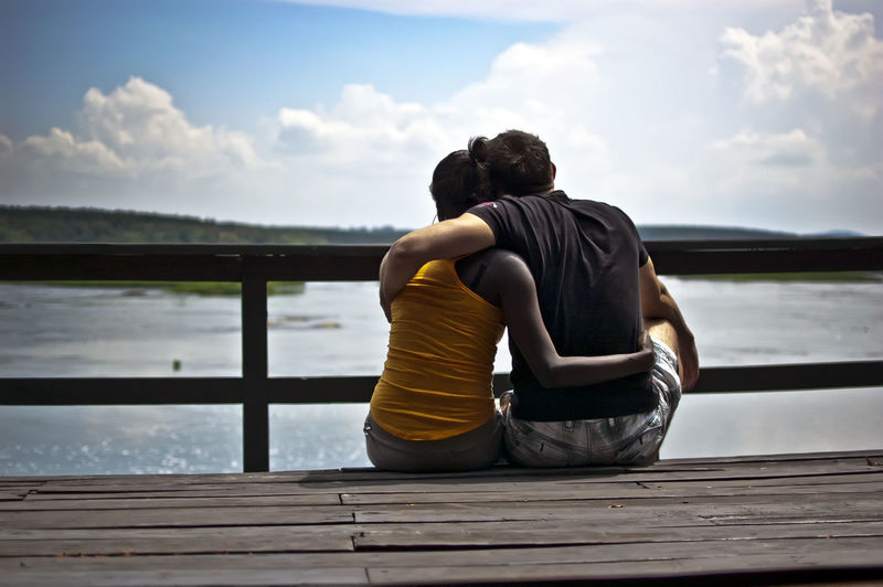 Rear view of couple sitting on pier over sea against sky