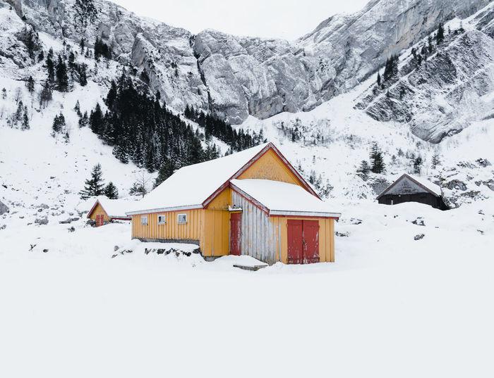 Houses on snowcapped mountain against sky