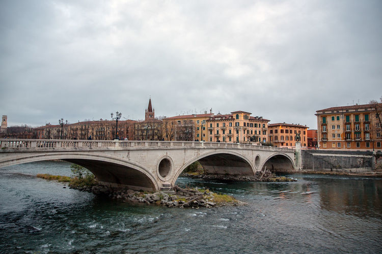 Arch bridge over river against sky in city