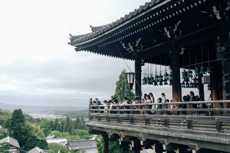 People visiting temple against sky