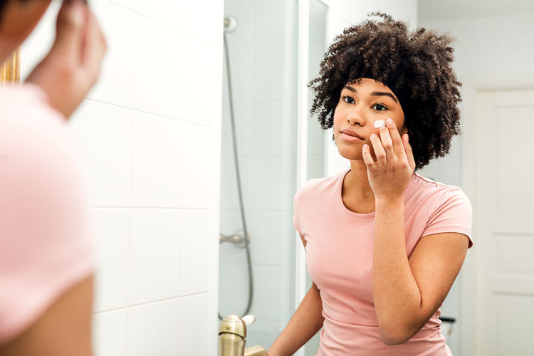 One Person Hairstyle Indoors  Beautiful Woman Healthy Skin Care Bathroom Cream Portrait Applying Mirror Reflection Young Morning Routine Daily Real People Mixed Race person Casual
