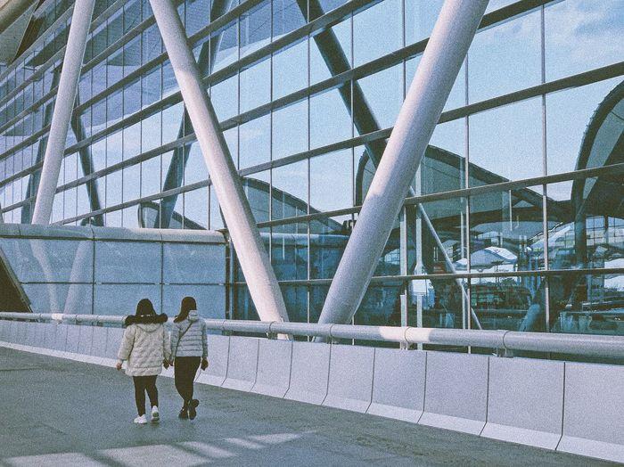 Rear view of people walking on bridge