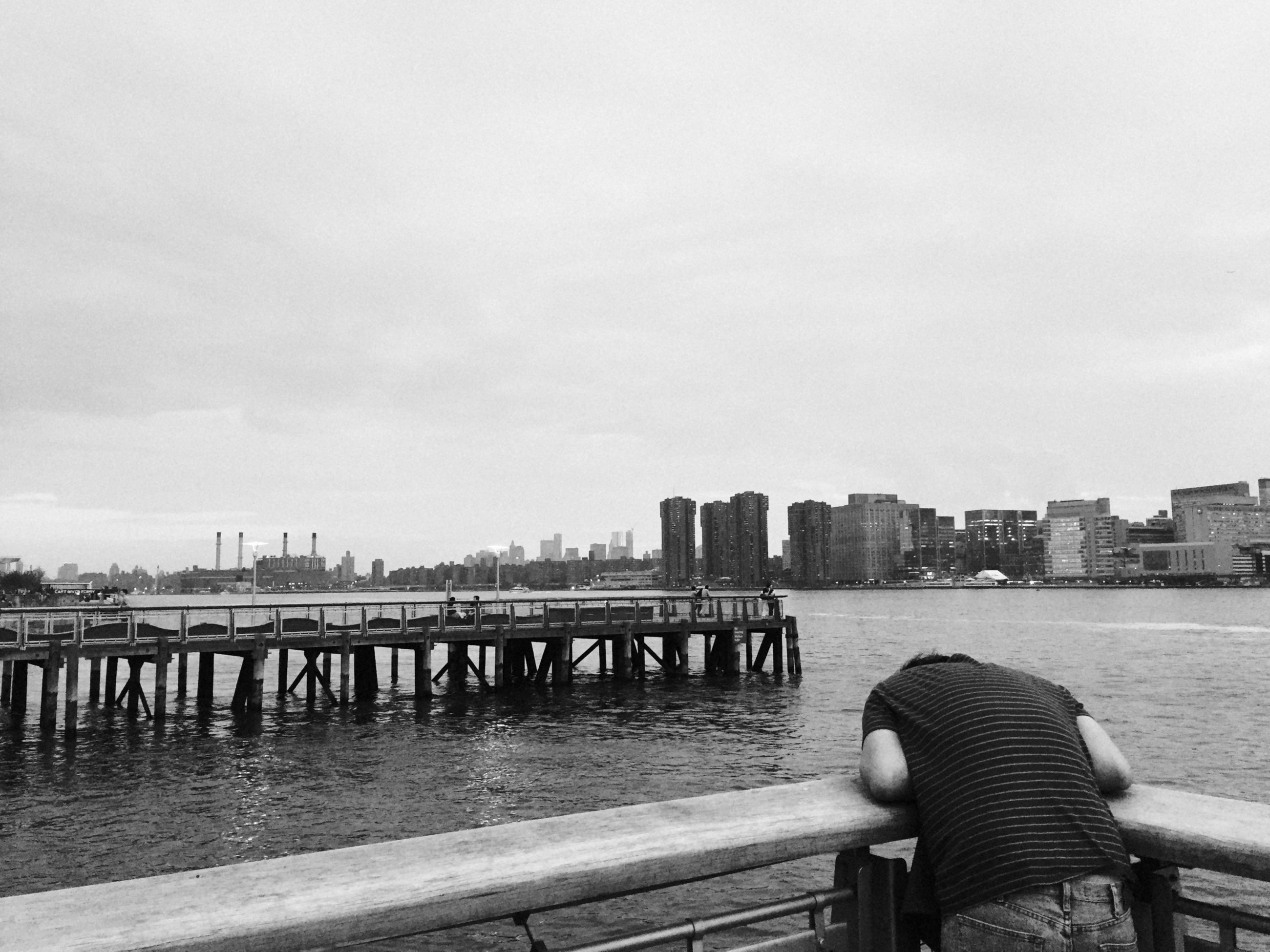 Rear view of man leaning on railing by river in city against clear sky