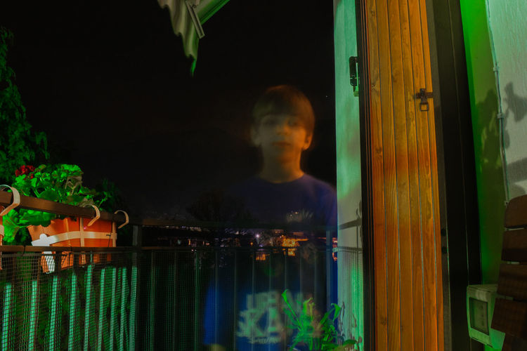 Boy Standing In Balcony At Night