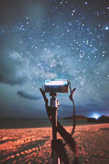 Camera on field against sky at night
