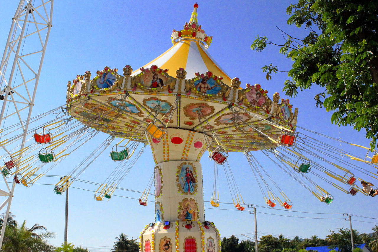 amusement park, arts culture and entertainment, amusement park ride, low angle view, fairground ride, clear sky, chain swing ride, carousel, leisure activity, enjoyment, day, outdoors, tree, fun, blue, carousel horses, no people, merry-go-round, sky