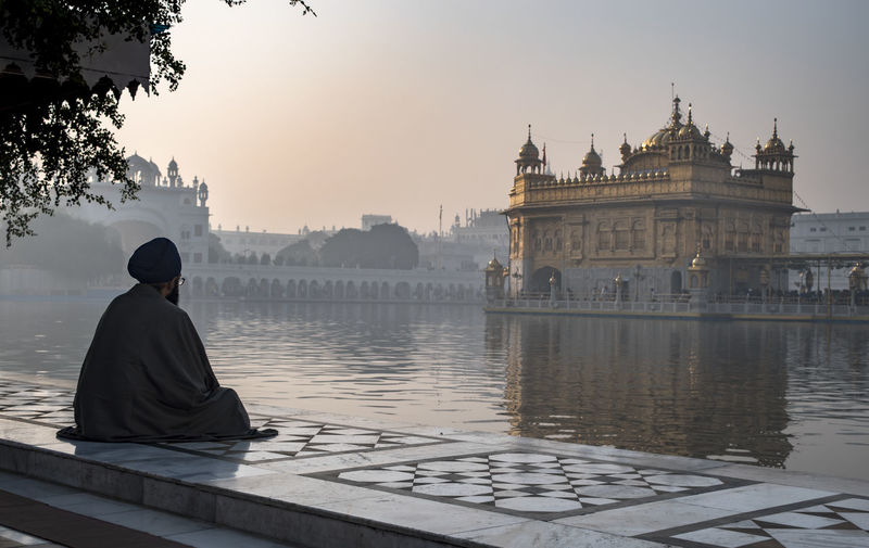 Man Looking At Golden Temple Against Sky During Sunrise