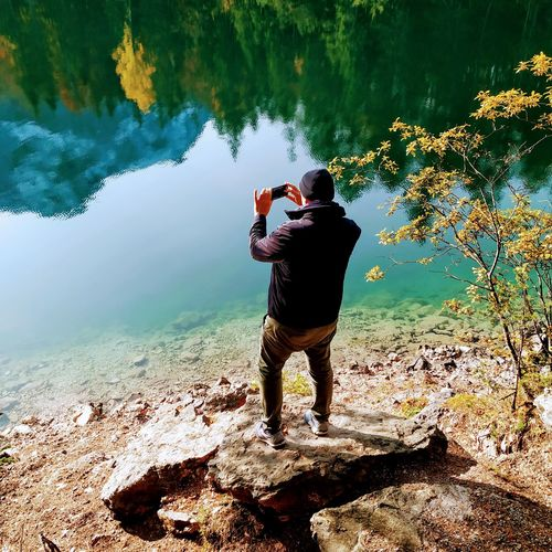 Rear view of man photographing lake