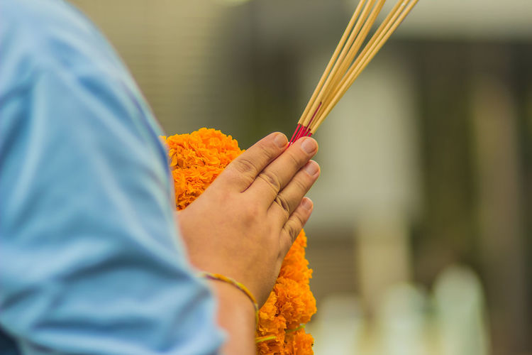 Cropped Hands Holding Incense Sticks With Floral Garland In Temple