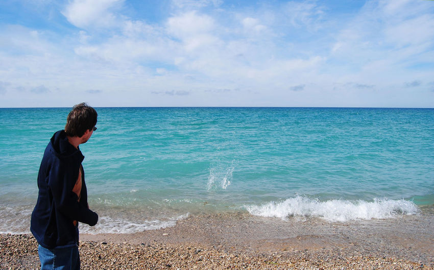 Rear View Of Man Skipping Stone On Lake Michigan Against Cloudy Sky