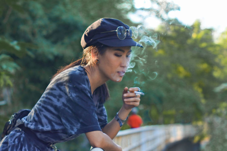 Young woman smoking cigarette against trees