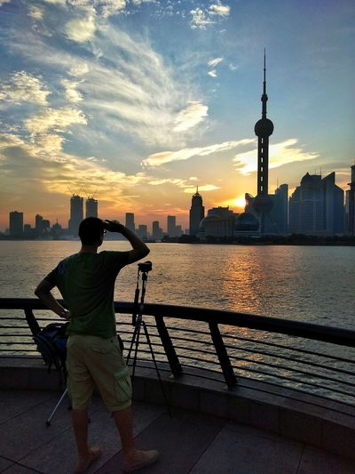 Rear View Of Man Looking At Oriental Pearl Tower During Sunset In City