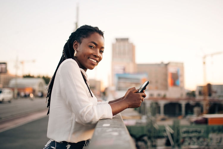 Side view portrait of young man using smart phone in city