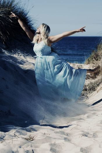 Woman Dancing On Sand Against Sea At Beach