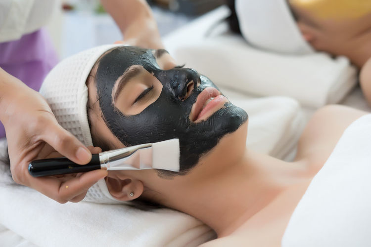 Cropped hand of massage therapist applying facial mask on young woman face in spa