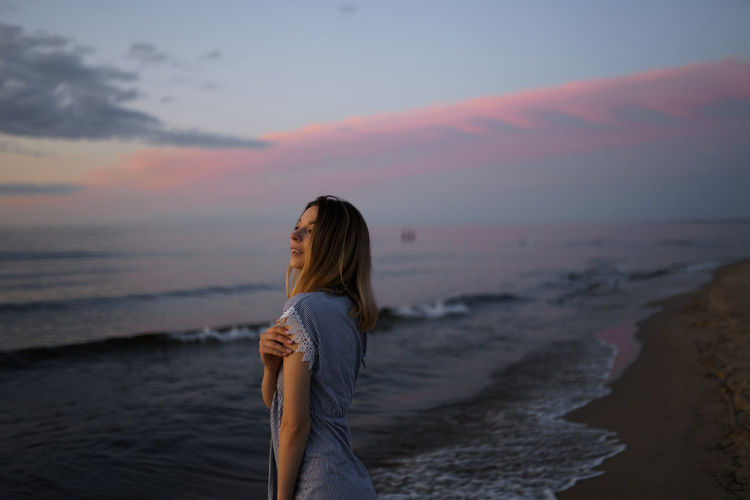 Woman looking away while standing at beach during sunset