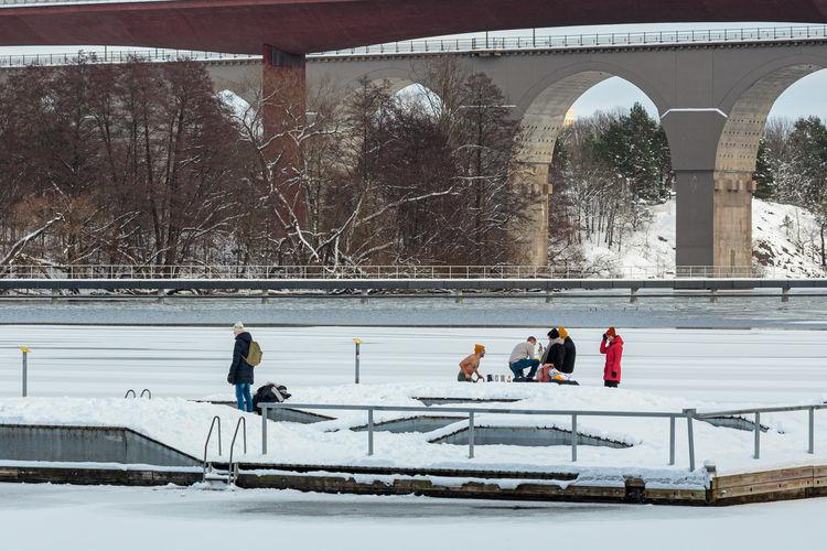 People walking on bridge during winter