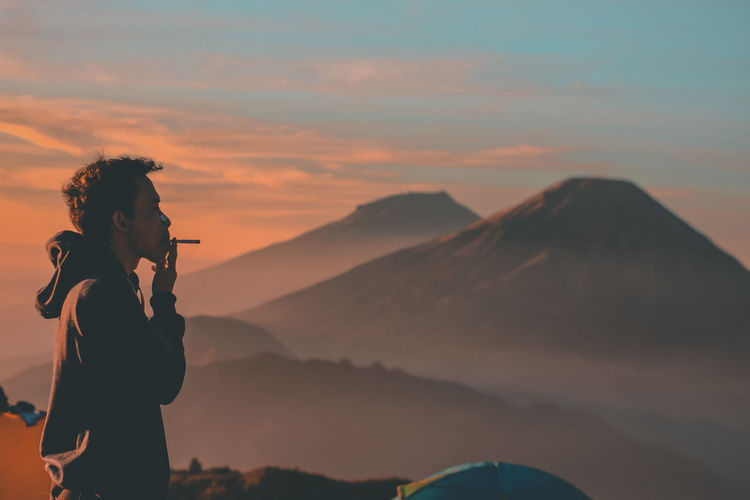 Side view of man smoking by mountains during sunrise