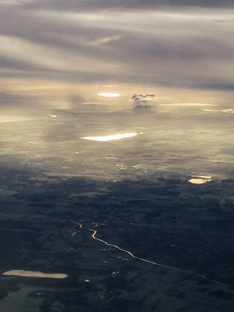AIRPLANE FLYING OVER SEA AGAINST SKY AT SUNSET