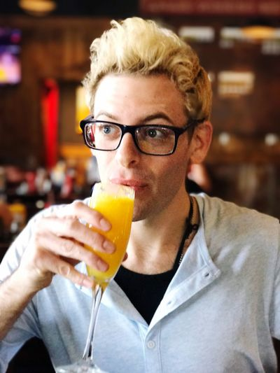 Young man looking away while drinking mimosa in bar