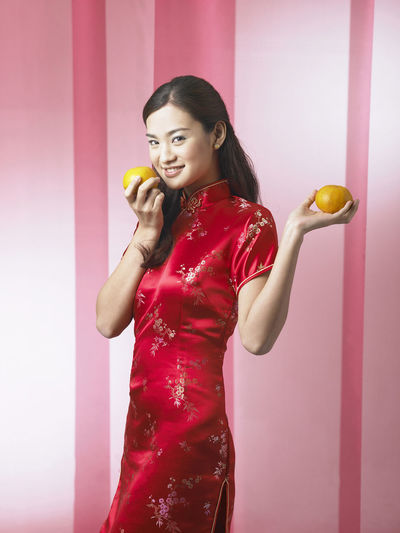 Portrait of smiling woman with oranges standing against backdrop