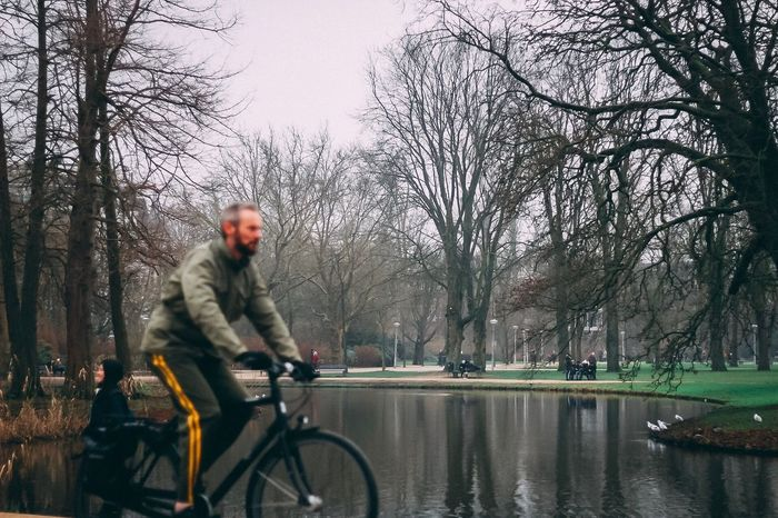 A city of cyclists Focus On Background Tree Real People Bare Tree Transportation Men Outdoors Bicycle Day Winter Land Vehicle One Person Lifestyles Nature Water Full Length Warm Clothing City Sky Only Men Adult