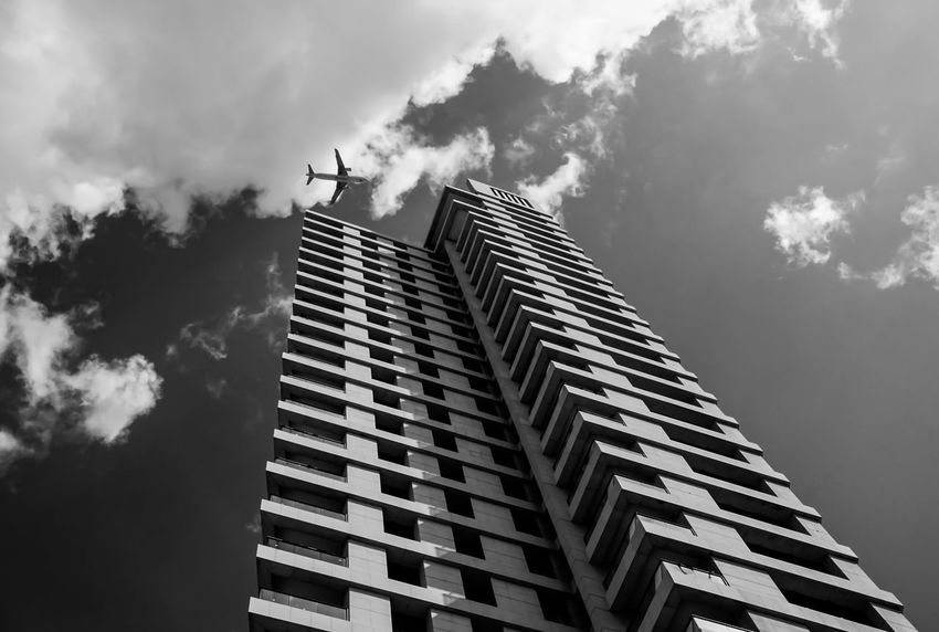 into the sky .. Aeroplane Aircraft Architecture Architecture_bw Krull&Krull Images Black And White Building Building Exterior Built Structure City Clouds Exterior Flying Israel Low Angle View Modern No People Office Building Sky Skyscraper Structure Tall - High Tel Aviv The Architect - 2017 EyeEm Awards The Photojournalist - 2017 EyeEm Awards Black And White Friday An Eye For Travel Mobility In Mega Cities Stories From The City